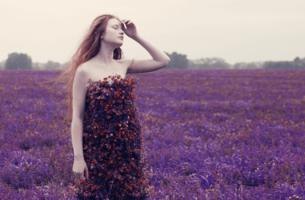 Schwere Zeiten - Frau in Blumenkleid auf Blumenfeld