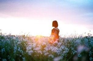 Alles überwinden - Eine Frau steht in einer Blumenwiese.