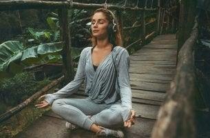 Frau in Lotusstellung hört Entspannungsmusik