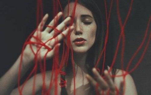 Eine Frau hat sich in einem roten Faden verhängt, der häusliche Gewalt und Missbrauch symbolisiert, aus denen wir uns nur schwer losreißen können.