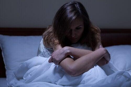 Eine Frau sitzt wach in ihrem Bett und kann nicht einschlafen