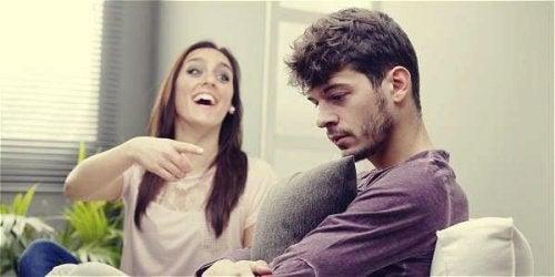 Eine Frau sitzt neben ihrem Freund und lacht ihn höhnisch aus.