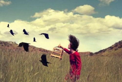 Eine Frau lässt Vögel aus einem Käfig in einem Feld frei.