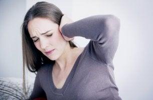 Tinnitus - Frau fasst sich ans Ohr