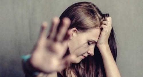 Häusliche Gewalt und Missbrauch - Eine Frau streckt die Hand vor sich weg und schaut traurig zur Seite.