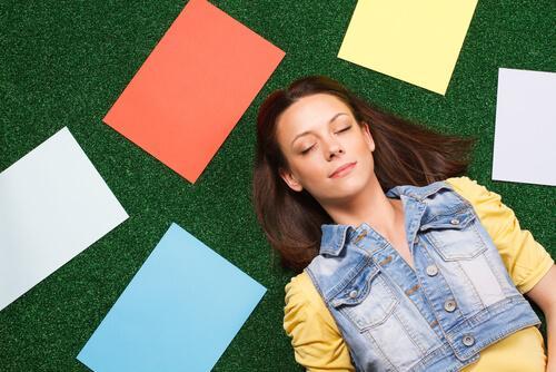 Frau liegt entspannt auf einem mit Zetteln bedeckten Boden