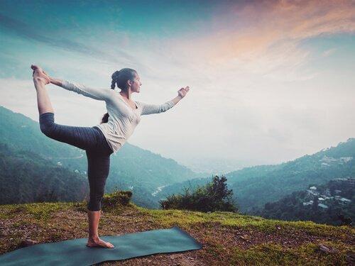 Eine Frau praktiziert auf einer Matte in der Natur Yoga.