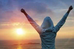 Intrinsische Motivation - Frau, die ihre Arme in die Luft streckt