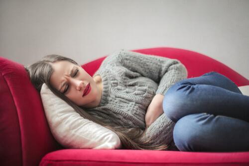 Frau, die mit Bauchschmerzen auf der Couch liegt