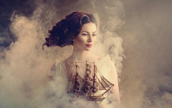 Dunkelhaarige Frau hält ein Schiff in der Hand