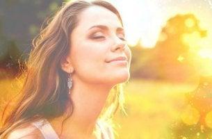 Wahre Schönheit kommt von innen - Frau mit geschlossenen Augen genießt das Sonnenlicht.
