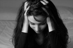 Emotionale Erschöpfung - Frau schlägt die Hände über dem Kopf zusammen