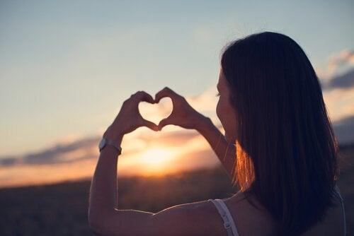 Frau formt mit ihren Händen ein Herz