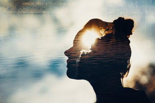 Silhouette einer Frau gegen die Sonne und einen See