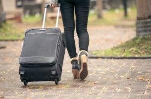 Eine Frau zieht ihr Gepäck über den Gehweg.