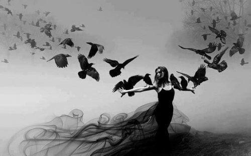 Eine Frau wird von Rabenvögeln angeflogen, die sich auf ihren Armen niederlassen