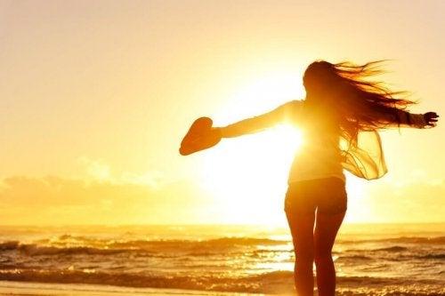 Frau am Meer mit offenen Armen und einem Herz in der Hand