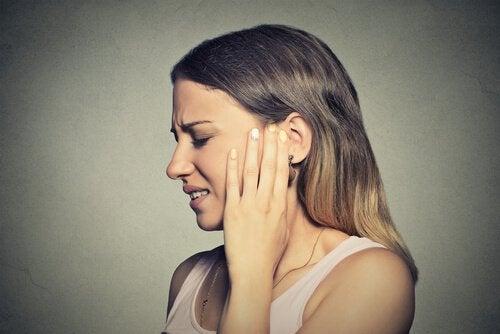 Frau, die an Tinnitus leidet, greift sich ans Ohr