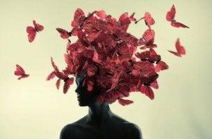 Frau, auf deren Kopf rote Schmetterlinge sitzen, bemüht sich, gesund zu denken