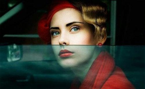 Frau mit roter Jacke schaut aus dem Autofenster