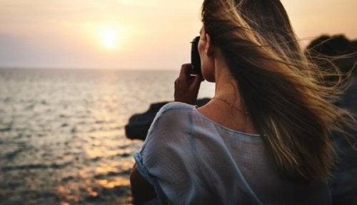 Eine Frau macht ein Foto vom Sonnenuntergang über dem Meer.