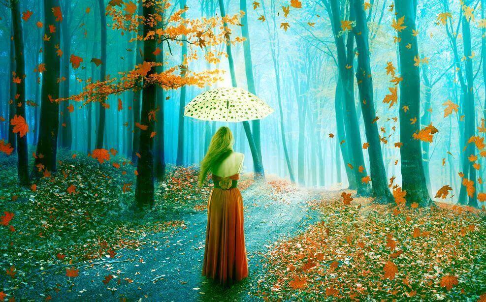 Frau mit Schirm im Herbstwald
