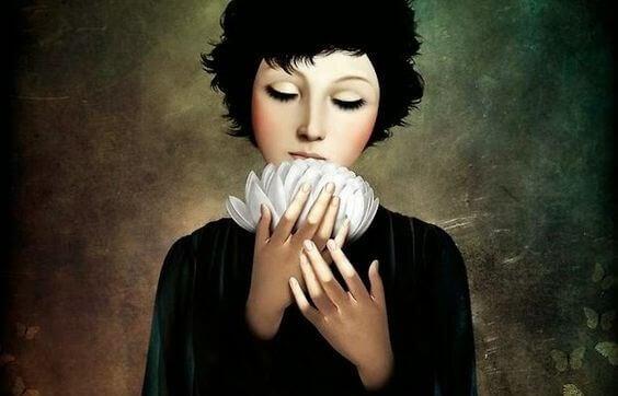 Ein Bild einer Frau, die eine weiße Blume in ihren Händen hält