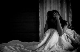 Panikattacken in der Nacht - Eine Frau sitzt aufrecht im Bett und scheint von einer Panikattacke gepeinigt zu sein.