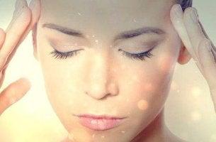 Nahaufnahme vom Gesicht einer Frau; sie hat ihre Augen geschlossen und übt Selbsthypnose.