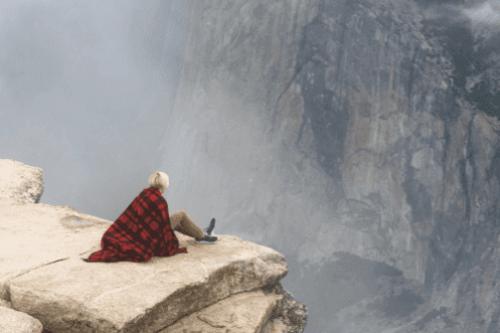 Frau sitzt an einer Klippe