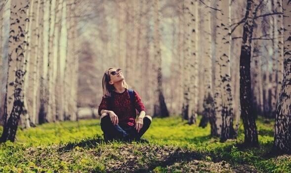 Frau sitzt im Wald und schaut in den Himmel