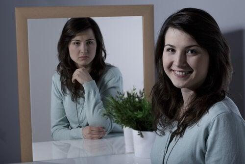 Eine Frau schaut in die Kamera und lächelt, aber ihr Spiegelbild zeigt sie nachdenklich.