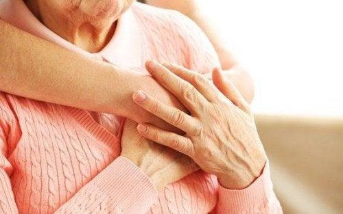 Niedergeschlagenheit bei Senioren begegnen - Eine junge Frau umarmt eine ältere Frau von hinten, ihre Hände liegen aufeinander.
