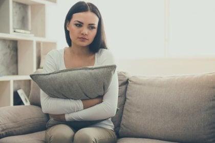 Frau umarmt gedankenverloren ein graues Kissen