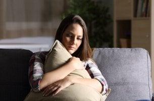 Kopfzerbrechen vermeiden - Frau umarmt Kissen und grübelt