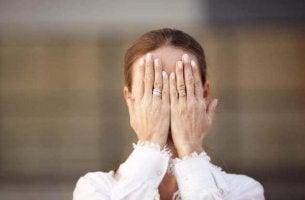Agnosie - Frau versteckt ihr Gesicht hinter ihren Händen.