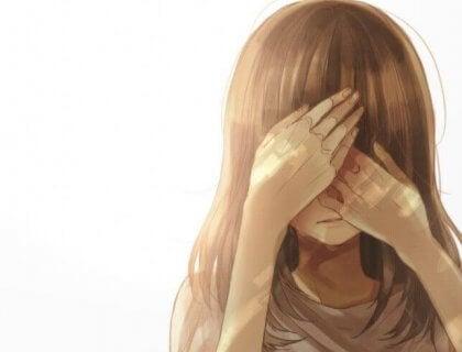 Ein Mädchen versteckt sein Gesicht hinter ihren Händen.