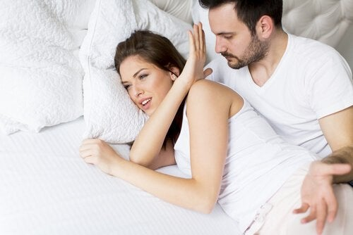 Eine Frau weist einen Mann im Bett zurück.