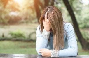Eine Frau will nicht zum Psychologen gehen und vergräbt verzweifelt ihren Kopf in ihrer Hand
