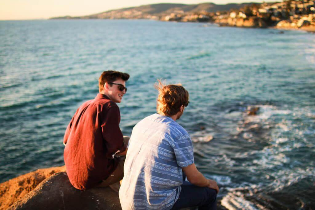 Zwei Freunde sitzen am Meer und unterhalten sich