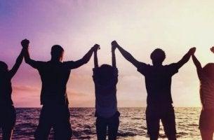 Arten von Freunden - Freunde sind am Strand und heben ihre Hände in die Höhe.
