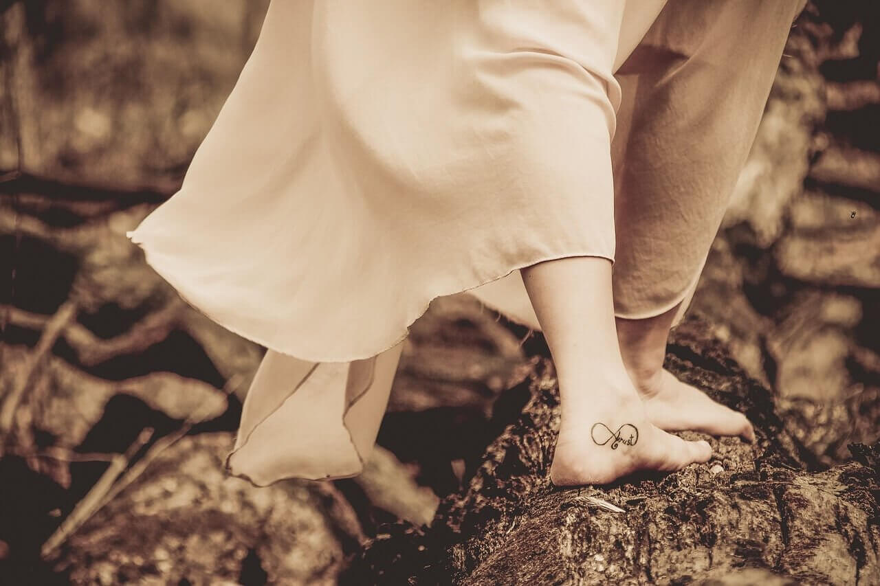 Tätowierter Fuss steht auf einem Baumstamm