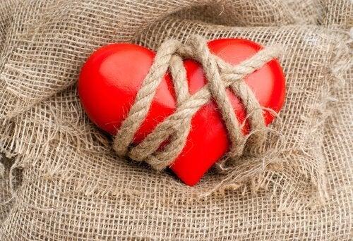 Gefesseltes Herz liegt auf Leinenstoff.