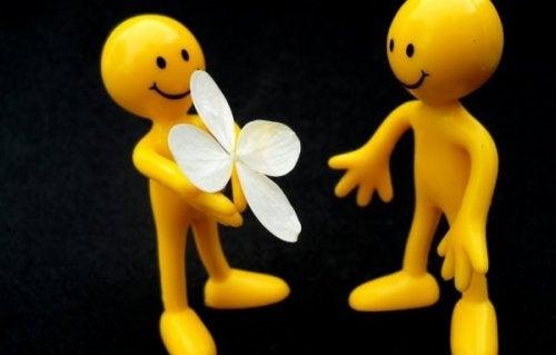 Eine gelbe Figur gibt einer anderen gelben Figur eine Blüte.