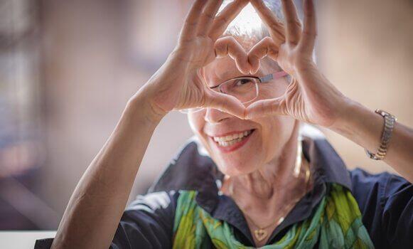 Gesundes Altern macht glücklich - ältere Dame formt mit ihren Händen ein Herz