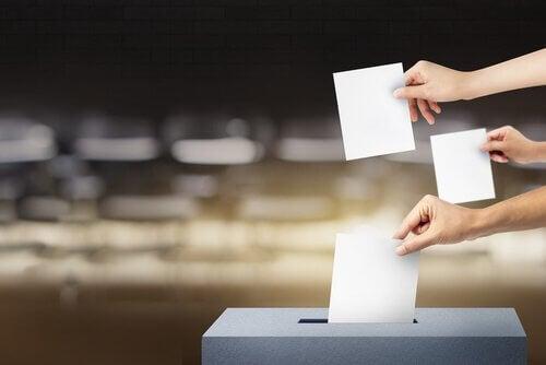 Drei Hände mit Wahlzetteln über einer Wahlurne