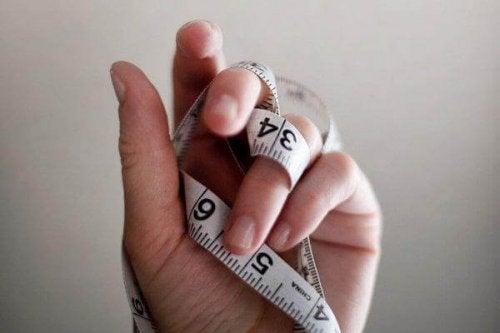 Eine Hand hält ein Maßband hoch, als Zeichen einer Essstörung