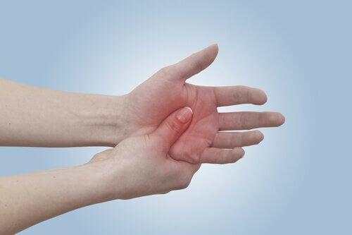 Frau hält schmerzende Hand