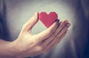 Nett zu sich selbst - Hand hält aus Papier gefaltetes Herz.