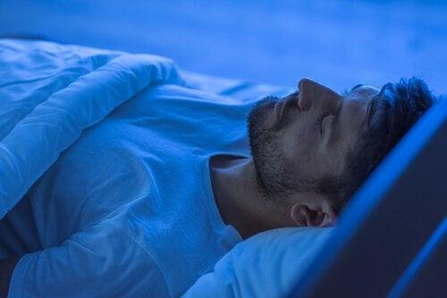 Ein Mann schläft in seinem Bett.